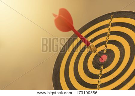 Red dart arrow with over blurred background. target of dartboard . metaphor to target business concept.