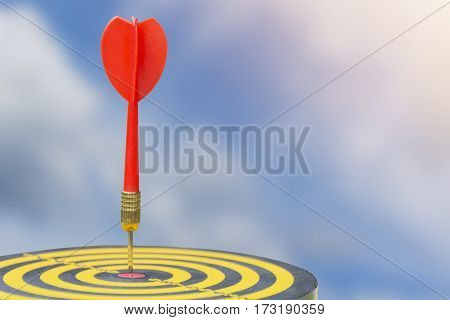 Red dart arrow with over blurred sky background. target of dartboard . metaphor to target business concept.