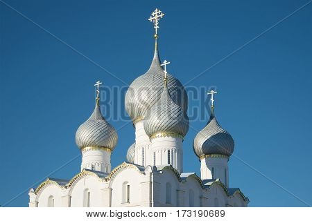 Domes of the Assumption Cathedral on blue sky background close-up. The Kremlin of Rostov Veliky. Golden ring of Russia