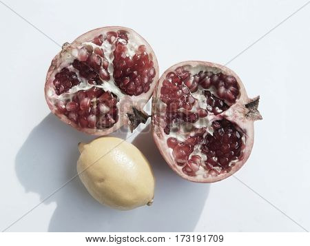 Cut into two halves of a pomegranate with red grains and yellow lemon