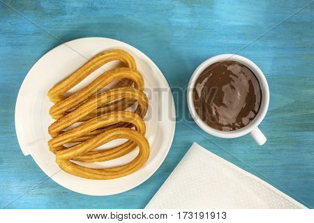 A plate of churros, traditional Spanish, especially Madrid, dessert, particularly for Sunday breakfast, with a cup of hot chocolate, shot from above on a turquoise table with a place for text
