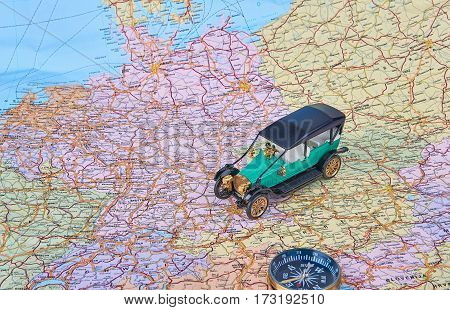 Image of travel concept. Old toy car on a European road map. On the atlas the compass lies.