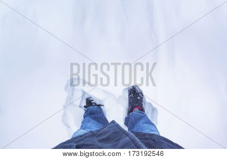 feet in shoes in the snow top view space for text the concept of a long winter cold First person point free space dress warmer