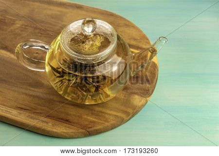 A photo of a teapot with a tea flower in it, with a place for text