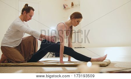 Thai massage - woman gets Thai traditional therapy for the spine, close up