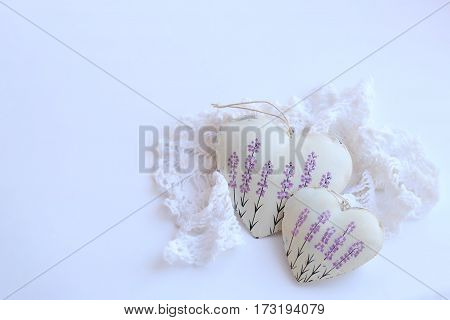 two hearts with lavender picture and lacy napkin on a white background. Soft focus bright colors.