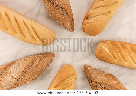 Loaves of rye and wheat bread, forming a frame on a white marble table with a place for text