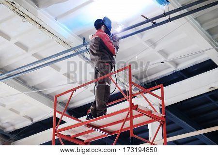 working as a welder welds a pipe