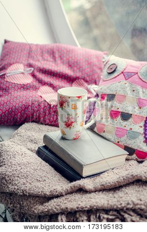 Warm and cozy window seat with cup of coffee or tea with books and cushions. Provence style rustic home decor. Lifestyle background in pink and purple tones.
