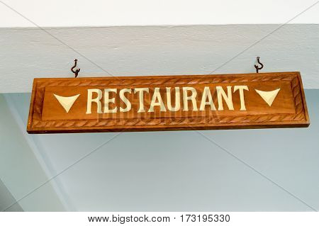 Directional board of the dining room chiselled in brown wood and white lettering