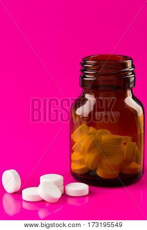 Pills bottle and medicine ampule on color background
