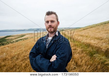 Portrait of farmer standing with arms crossed in the field on a sunny day