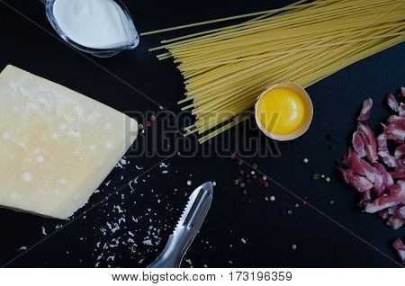 Ingredients for Pasta Carbonara on dark background. Set of products for pasta Carbonara - spaghetti bacon cream Parmesan cheese egg. Italian food concept. Top view.