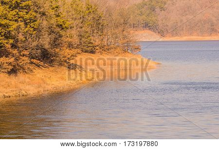 Winter landscape of lake in South Korea with barren trees on the far shore