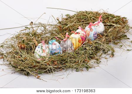 Easter colorful eggs with dry grass in the nest