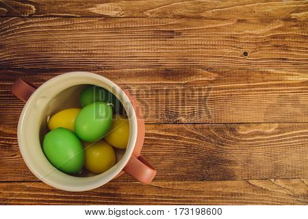 colored Eggs in a jar on wooden bacground