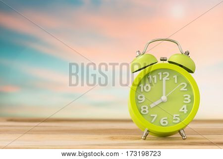 alarm clock on wooden table in the nature background