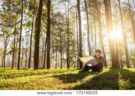 Traveler Man Hiker Walking Under The Rays Of The Sun In The Mountain Forest And Watching Map