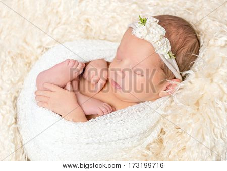 Adorable little girl napping in a nest out of a blanket, wearing a hairband, closeup