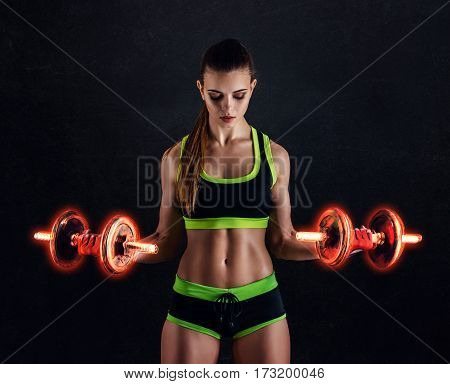 Young Athletic Woman In Sportswear With Fiery Dumbbells In Studio Against Black Background. Ideal Fe