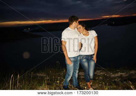 Loving Couple On Jeans And White Shirt On Beautiful Night Landscape.