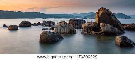 A rocky coastline at sunset looking out over the south China sea in Vung Lam Bay Vietnam.