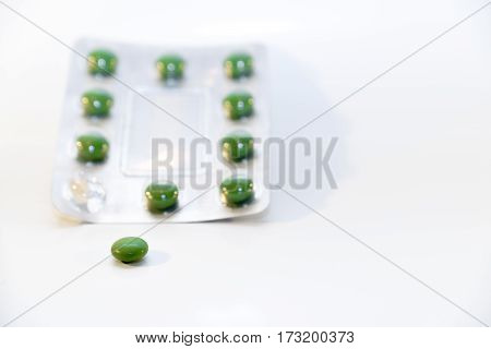 Green pills in blister package isolated on white