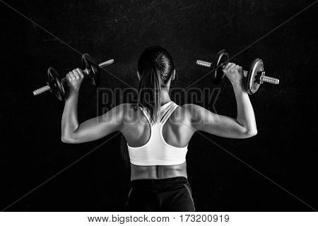Athletic Young Woman Doing A Fitness Workout Against Black Background. Attractive Fitness Girl Pumpi