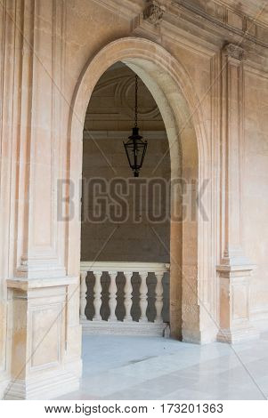 An arch and a lantern at the corridor of a Carl V Palace at Alhambra Granada (Andalusia Spain).