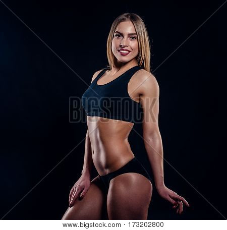 Sporty Girl With Great Muscles In Black Sportswear. Tanned Young Athletic Woman. A Great Sport Femal