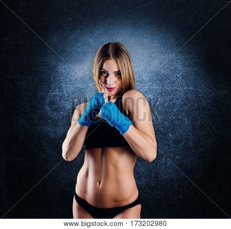 Attractive Athletic Woman With The Blue Boxing Wraps On Dark Background In Studio. Girl Ready For Fi