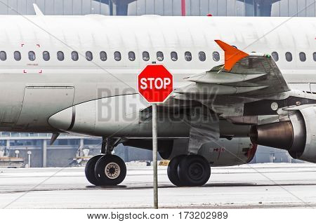Airplane in airport portholes and wing, in front of them stop sign