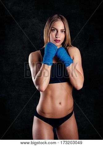 Attractive Athletic Woman With The Blue Boxing Wraps On Black Background In Studio. Girl Ready For F