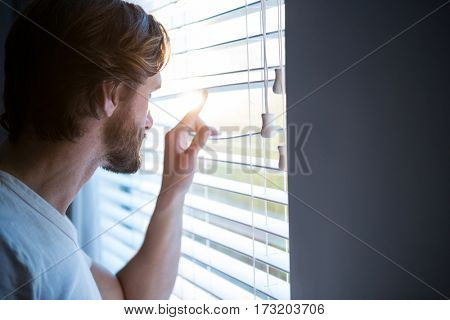 Man looking through window blinds after waking up at home