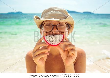 Excellent mood for a tropical vacation. Woman wearing glasses and hat holding dragon fruit pitahaya about closing the face smile.