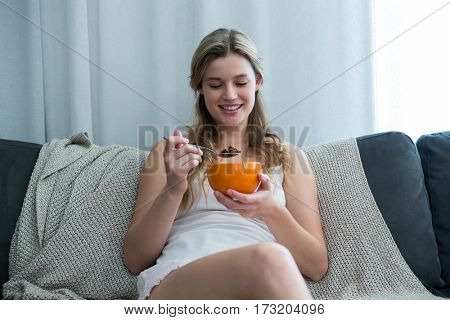 Woman having breakfast in living room at home