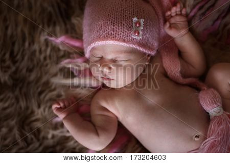 cute sleeper newborn baby girl in a pink cap on dark brown wool