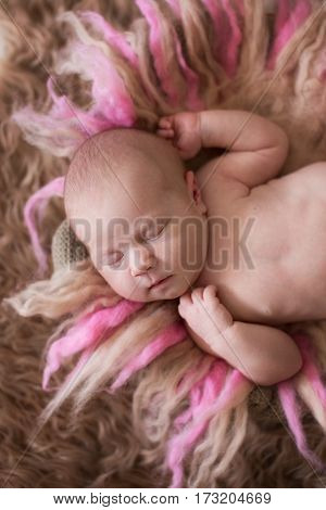 sweet sleeping newborn baby on a gentle pink background beige fur and wool