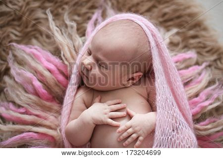 soft sleeper newborn baby girl in pink winding on background of beige and pink wool