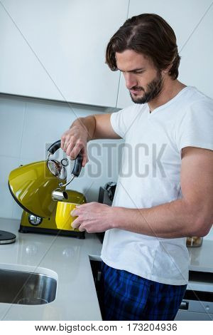 Man pouring coffee into cup in kitchen at home