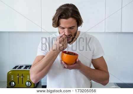 Man having breakfast in kitchen at home