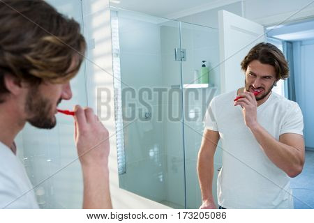 Man looking in mirror while brushing her teeth in bathroom at home
