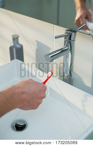 Man washing his toothbrush under sink in bathroom at home