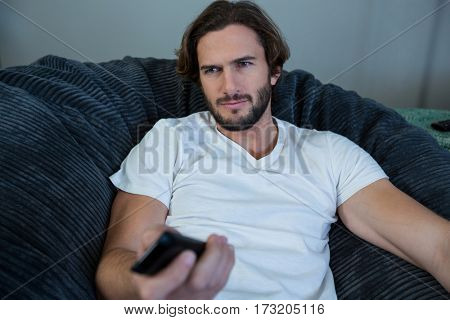 Man changing a channel while watching tv in living room at home