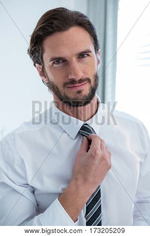 Man adjusting a tie in bedroom at home