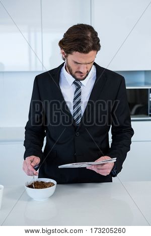 Businessman reading newspaper while having breakfast in kitchen at home
