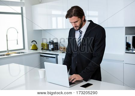 Businessman using laptop in kitchen at home