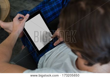 Man using digital tablet in living room at home