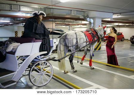 Woman in long dress stands near horse, coach and coachman in underground parking