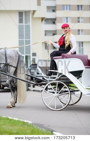 Coachman blonde sits on trestles of couch with horse near residential buildings